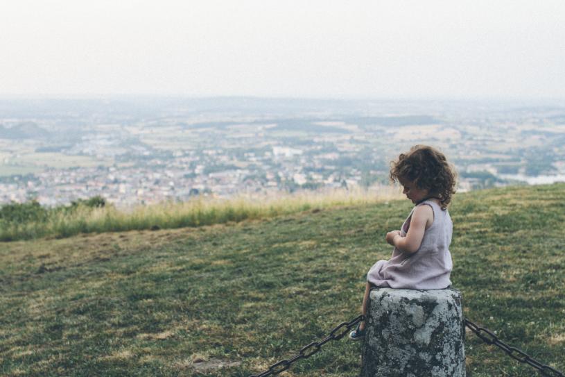 Een kindje kijkt met open aandacht uit over de wereld